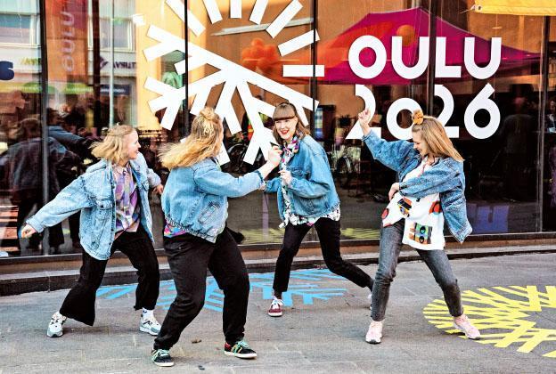 Neljä tyttöä tanssimassa Oulu2026-logon edessä.