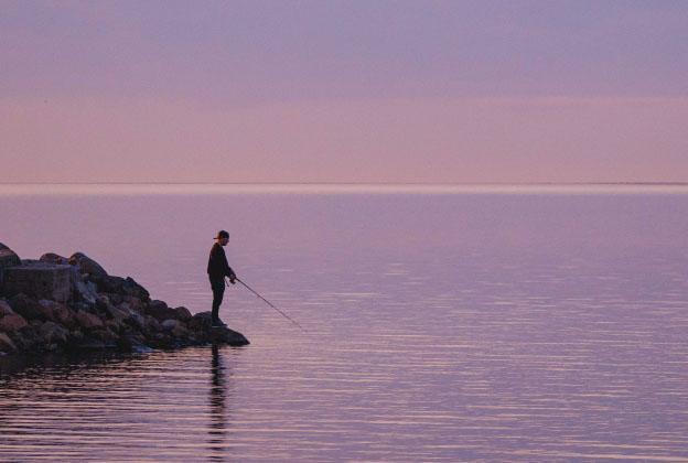 Ihminen kalastamassa yksin tyynen veden äärellä.