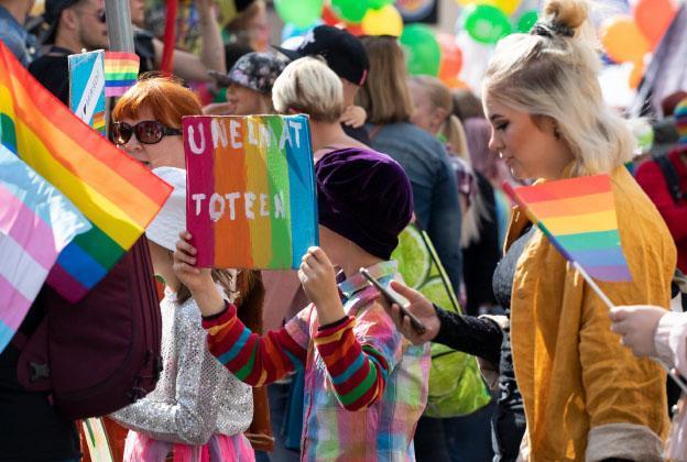 Iloisia ihmisiä Pride-lippujen ja -kylttien kanssa.
