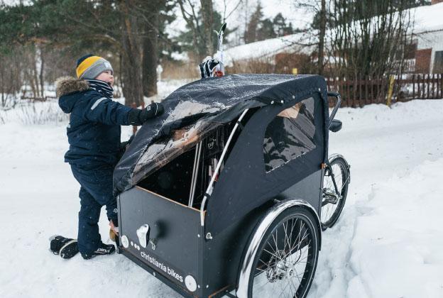 Lapsi lumessa laatikkopyörän kanssa.