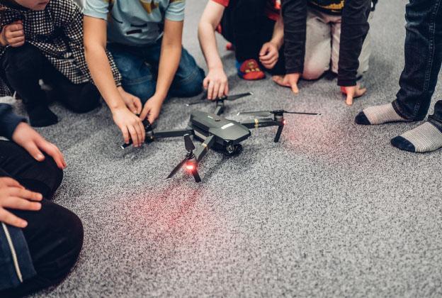 Lasten käsiä dronen ympärillä.
