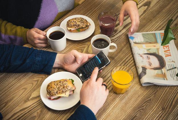 Kaksi henkilöä aamiaispöydässä, toinen selaa Oura-sormuksen uniraporttia.