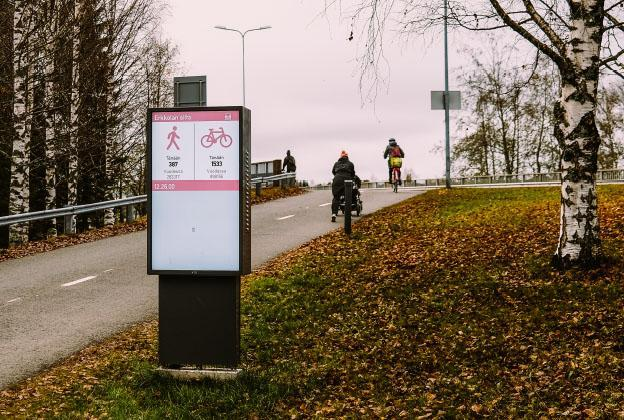 Ihmisiä pyöräilemässä pyöräilydatanäytön ohi syksyllä.
