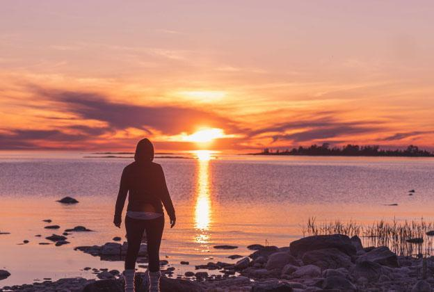 Ihminen rannalla auringonlaskussa.